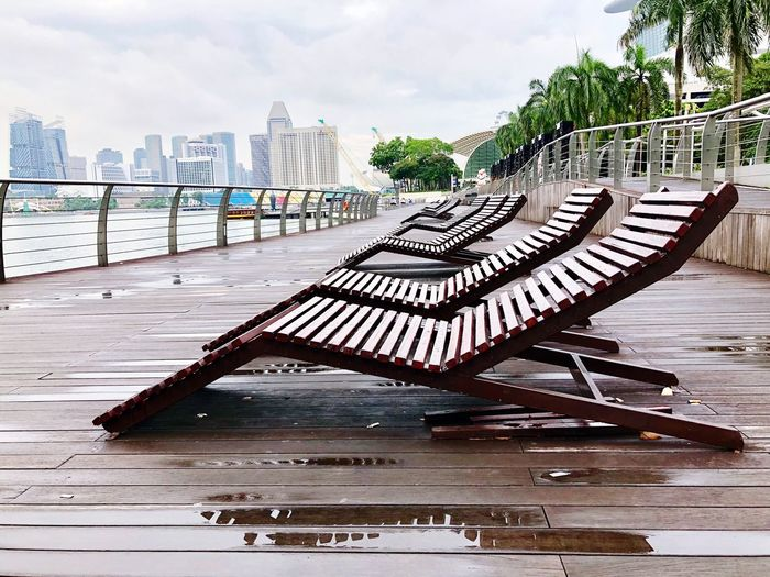 Wooden Bench On Pier By River Against Sky In City