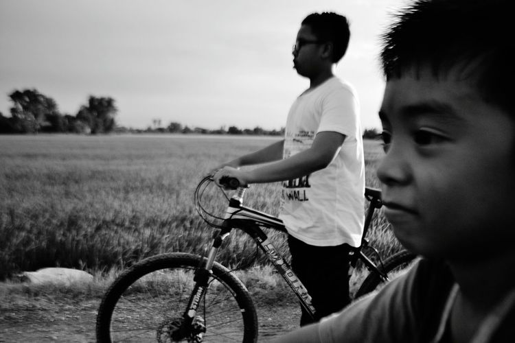 Side view of boy riding bicycle against sky
