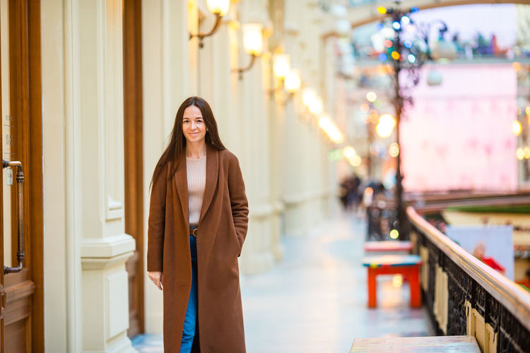 Portrait of woman standing on footpath by building