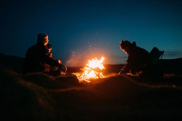 PEOPLE SITTING ON BONFIRE AGAINST SKY
