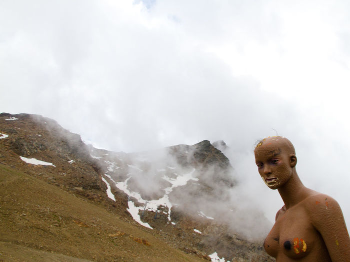 Full length of shirtless man in mountains against sky
