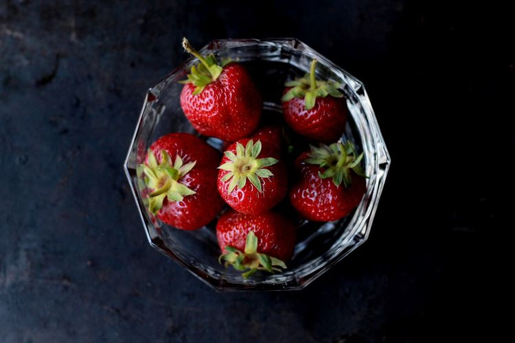 Close-up of strawberries in bowl against black background