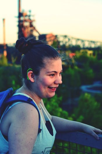 Side view of smiling teenage girl looking away during sunset
