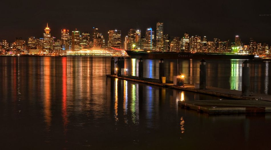 Scenic View Of Sea In Front Of Illuminated Cityscape At North Vancouver