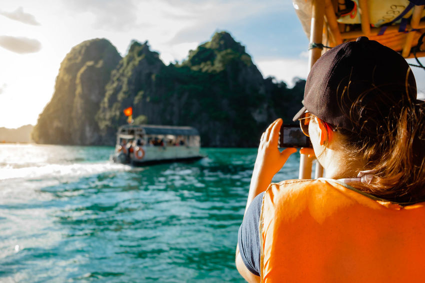 Snapping some memories. Taking Photos Woman Adventure Beauty In Nature Day Headshot Leisure Activity Lifestyles Mountain Nature Nautical Vessel One Person Outdoors People Real People Rear View Scenics Sea Sky Sunset Water