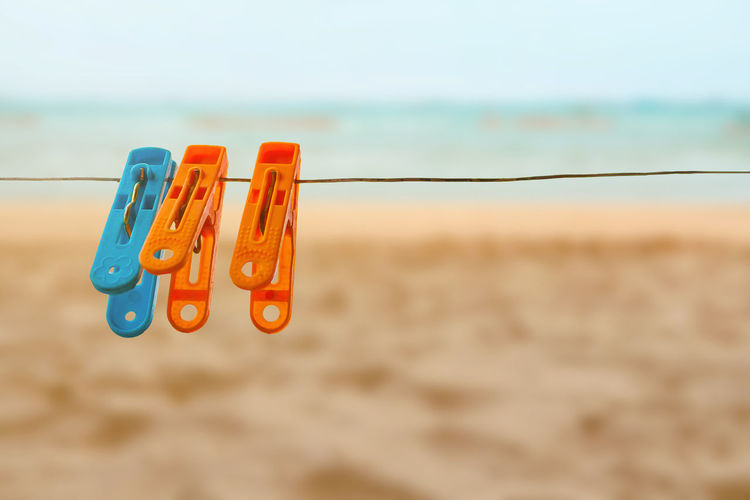 Concept colorful clothespin one blue two oranges pin with sling on nature sea and beach background Absence Beach Clip Close-up Clothesline Clothespin Day Focus On Foreground Hanging Land Multi Colored Nature No People Orange Color Outdoors Rope Sand Sea Sky Water