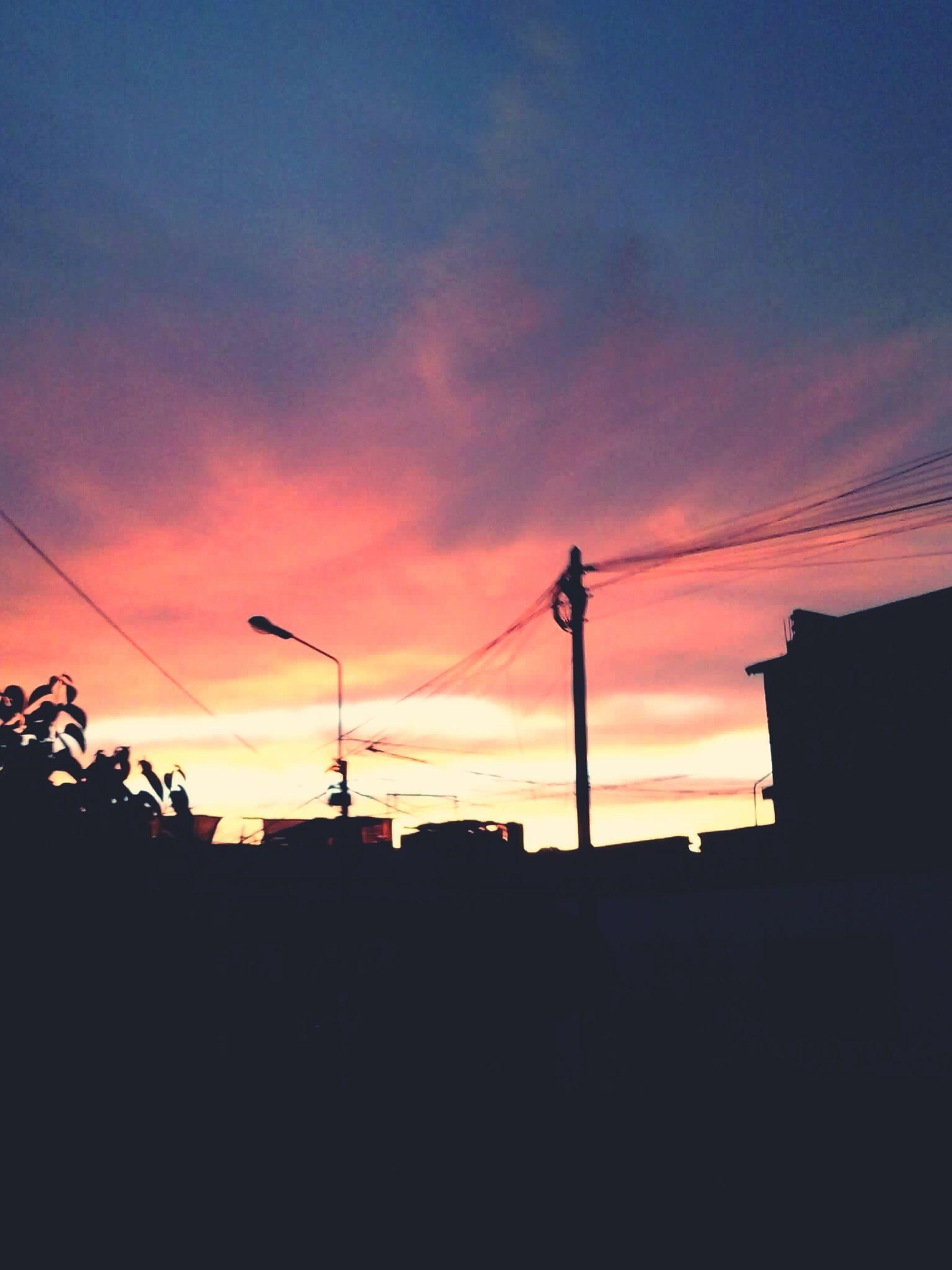 sunset, silhouette, building exterior, architecture, built structure, sky, orange color, low angle view, cloud - sky, street light, power line, house, building, cloud, residential structure, city, dusk, dark, residential building, dramatic sky