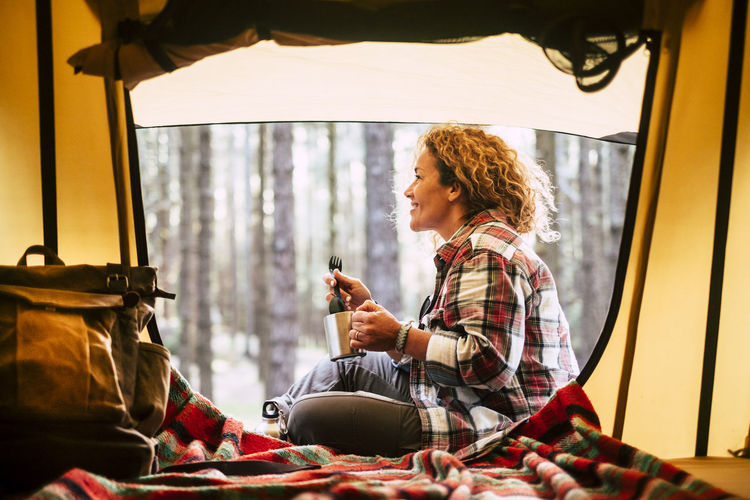 Side view of smiling woman holding mug while sitting by tent in forest
