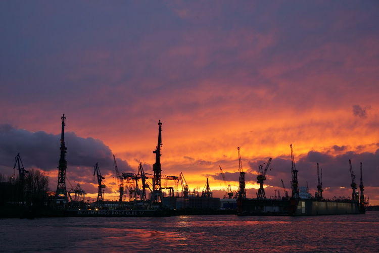 Commercial dock against cloudy sky during sunset