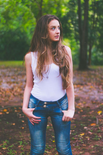 Beautiful Woman Casual Clothing Day Forest Front View Leisure Activity Lifestyles Long Hair Looking At Camera Nature One Person Outdoors Portrait Real People Standing Tree Young Adult Young Women