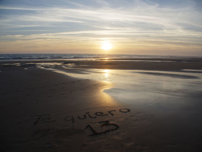Text on sand at beach against sky during sunset