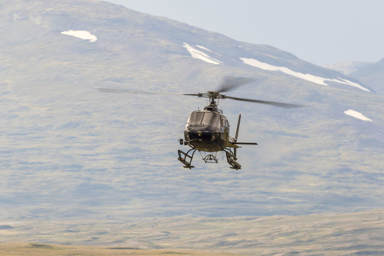 Helicopter flying in a mountain landscape in the wilderness