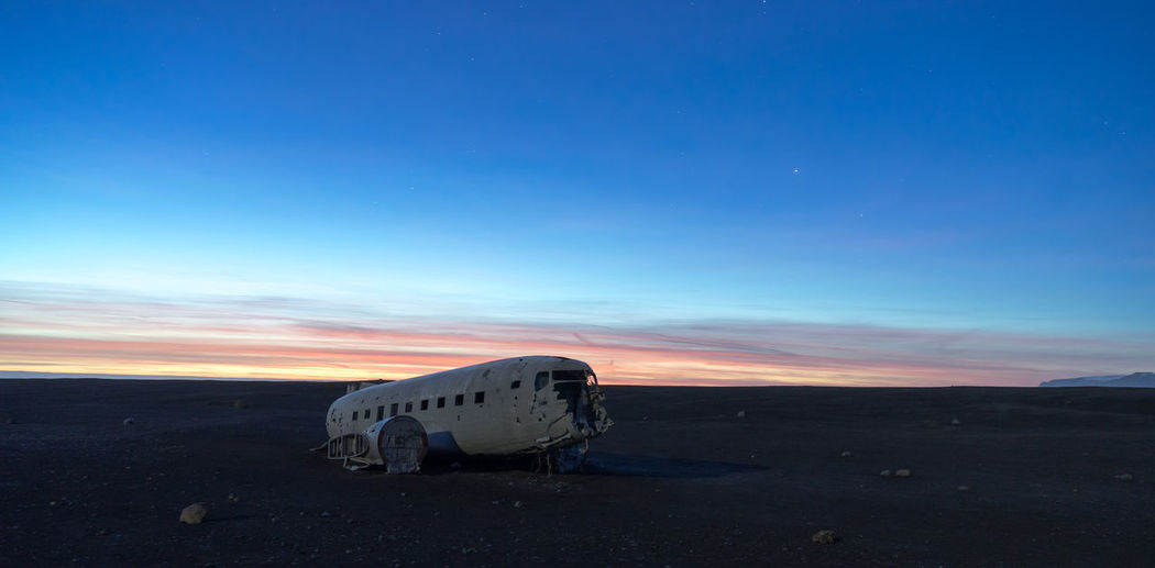 Abandoned airplane against sky during sunset