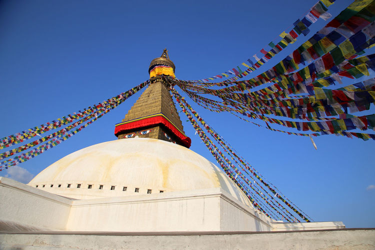 Low angle view of prayer flags on bodnath stupa against sky