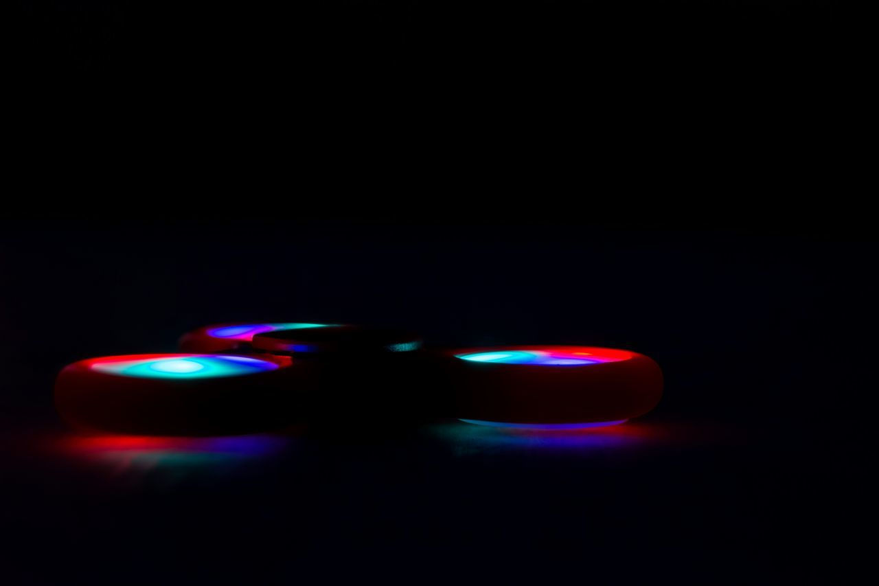 Close-Up Of Illuminated Fidget Spinner Against Black Background