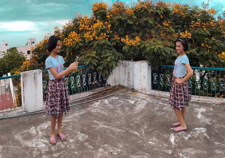 Full length of cute girl taking picture of sister on terrace against tree