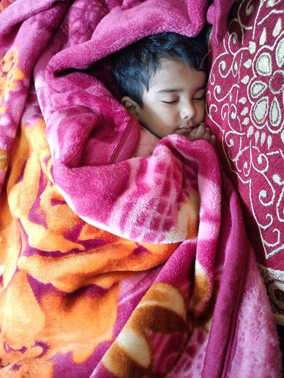 High angle view of cute baby sleeping on bed
