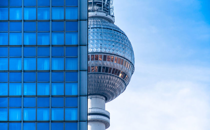 Low angle view of fernsehturm by building against sky