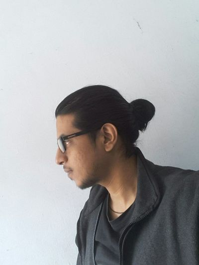 Close-up of hipster wearing eyeglasses against wall
