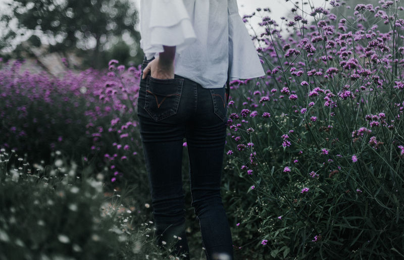 Midsection Of Woman With Hand In Back Pocket Standing Amidst Flowering Plants On Field