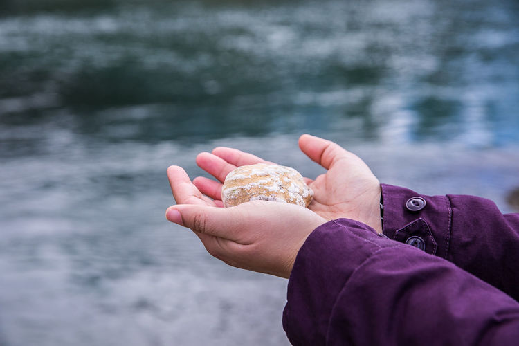 Close-up of man holding rock against lake