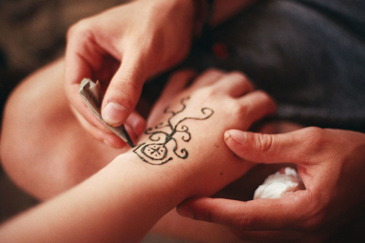 Cropped image of hands applying henna to person