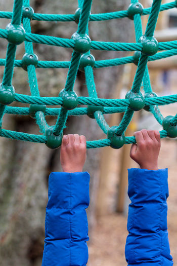 Cropped hands of child hanging on rope