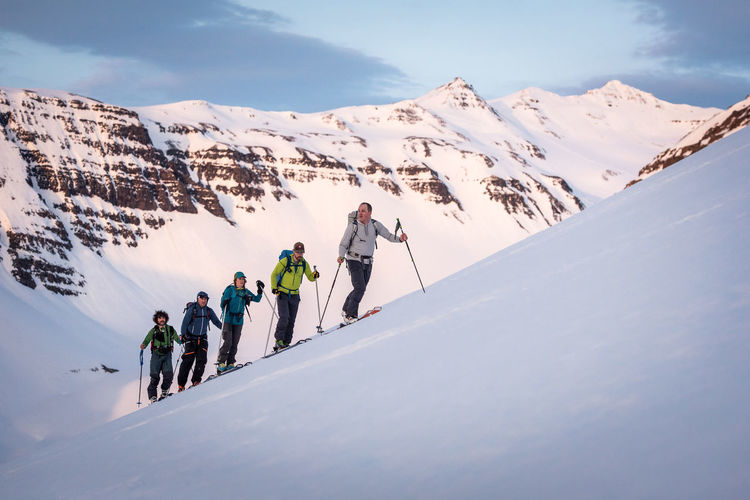 People walking on snowcapped mountains during winter