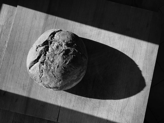 Ein Laib Brot auf einem Holzbrett Table Shadow Sunlight Indoors  Wood - Material High Angle View No People Textured  Close-up Day Freshness bread
