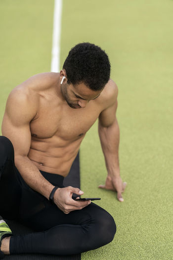 Midsection of shirtless man looking at camera