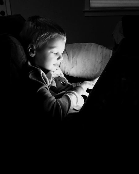 Boy using digital tablet on bed at home