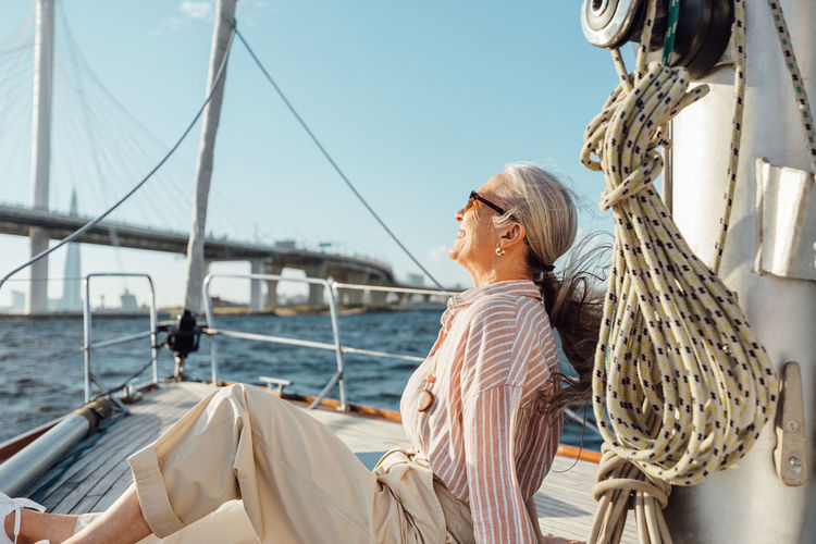 Smiling senior woman sitting on boat in sea against sky