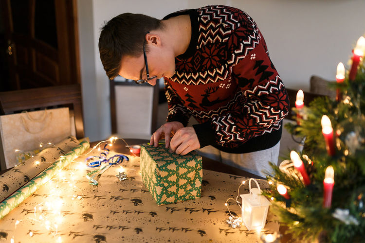 Midsection of man holding christmas lights on table