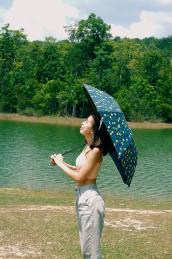 Woman with arms outstretched standing on rock by lake