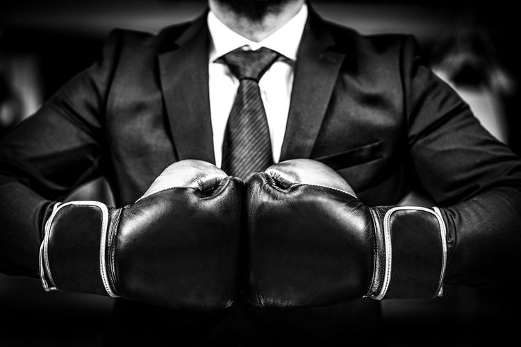 Midsection Of Businessman Wearing Boxing Gloves