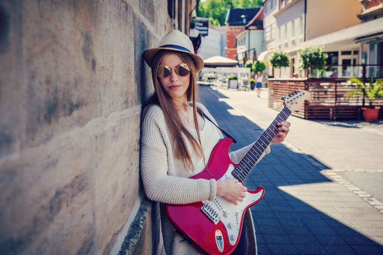 Portrait of young woman playing guitar while standing by wall