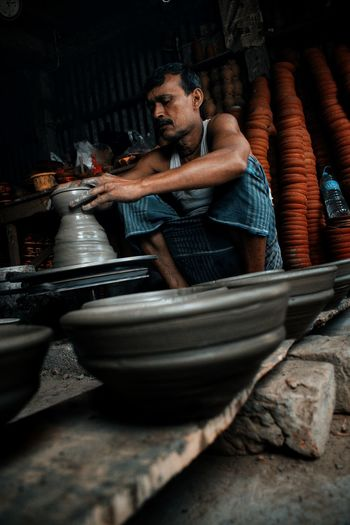 Low angle view of man making pottery in workshop
