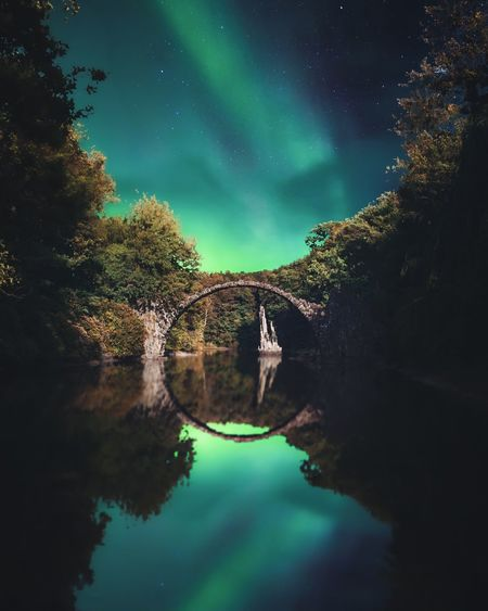 Reflection of arch bridge and trees in calm lake against aurora borealis in sky