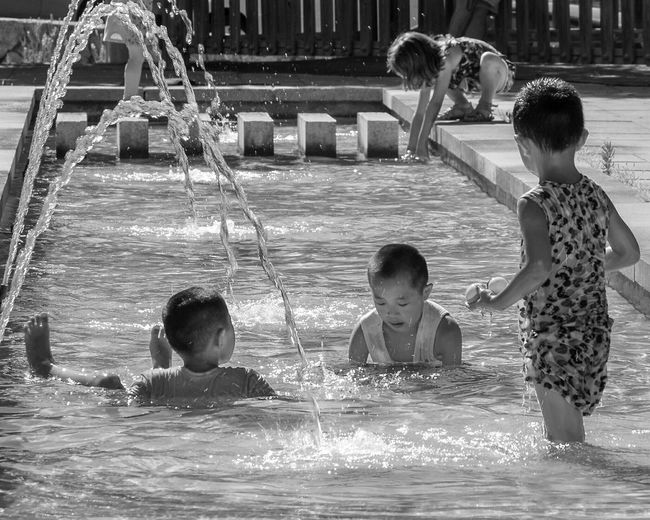 Street Scene Sunny Summer Public Fountain Water Child Childhood Swimming Pool Boys Happiness Girls Friendship Togetherness Playing Summer In The City