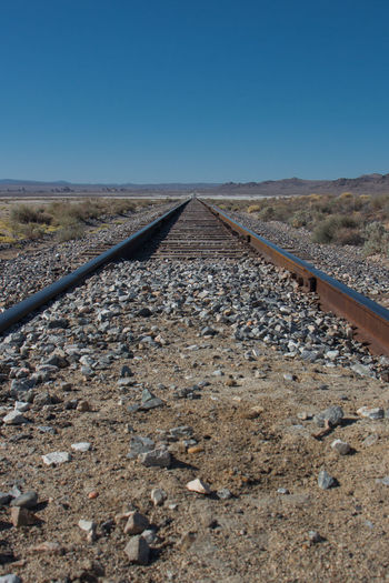 Railroad track against clear blue sky