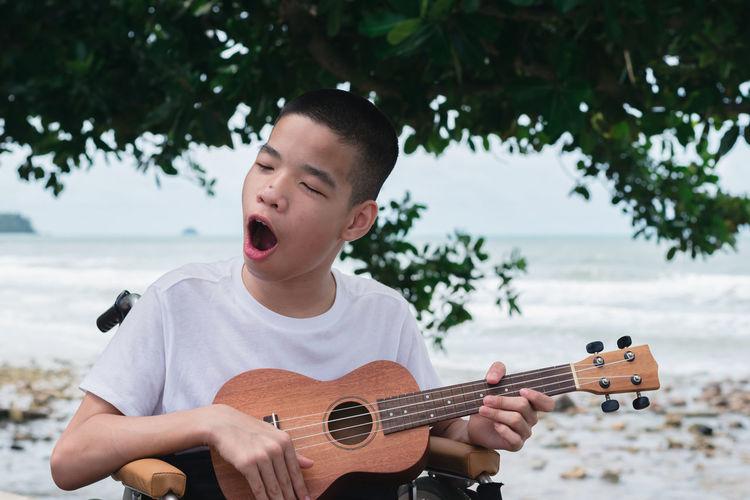 Cheerful boy playing ukulele against tree