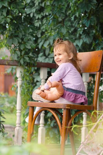 Girl sitting on chair in yard