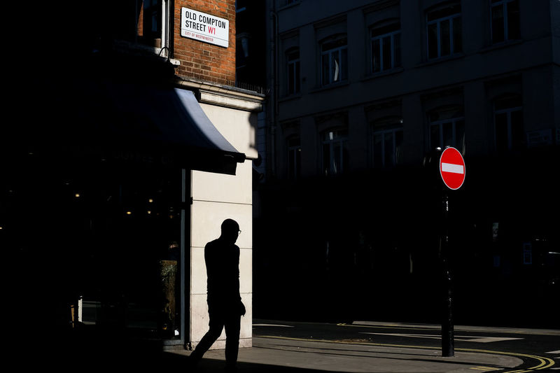 Silhouette man walking on street corner with sun against buildings