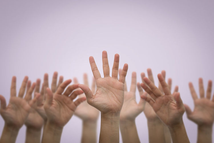 Group of people with arms raised against sky