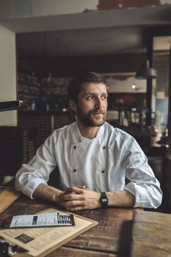 Portrait of young man sitting at restaurant