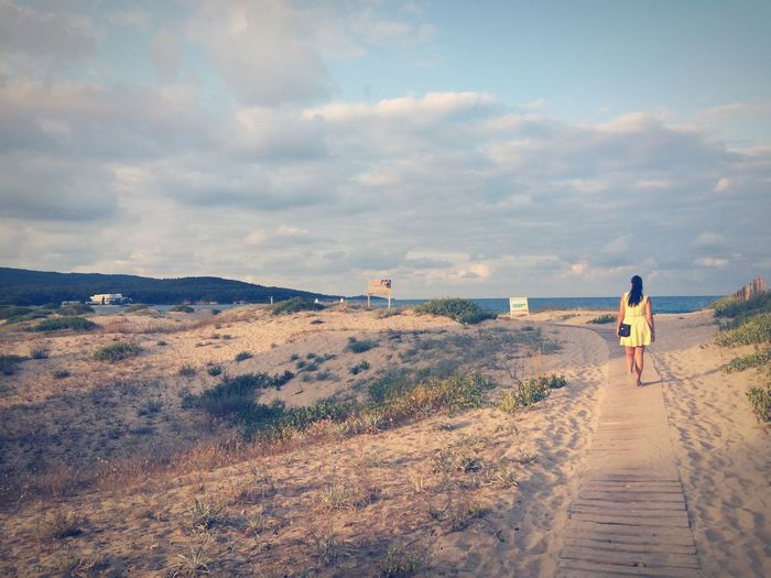 A woman Real People Sky Full Length Cloud - Sky Rear View One Person Leisure Activity Lifestyles Outdoors Walking Scenics Day Nature Mountain Beauty In Nature Men The Way Forward Women beach sea