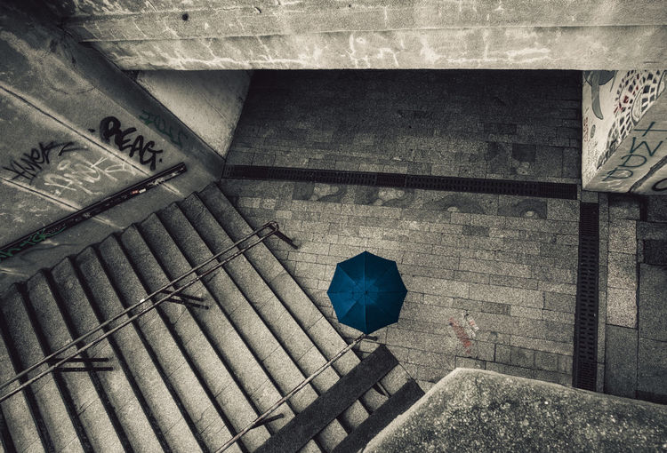 I was standing on the edge waiting for the perfect moment of a person crossing the frame at the right place fully covering herself. City Dark Rain Underpass Blue Day Dengler Dirty Person Snapshopped Street Subway Umbrella Umbrellas Urban