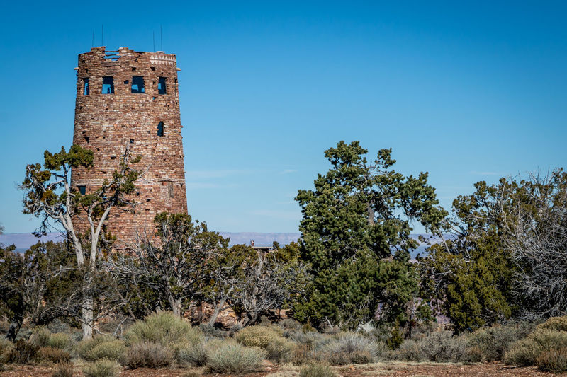 Desert View Tower at Grand Canyon Arizona Brick Wall Desert View Tower Grand Canyon Architecture Blue Building Building Exterior Built Structure Clear Sky Day History Land Low Angle View No People Old Outdoors Plant Sky Sunlight The Past Tree