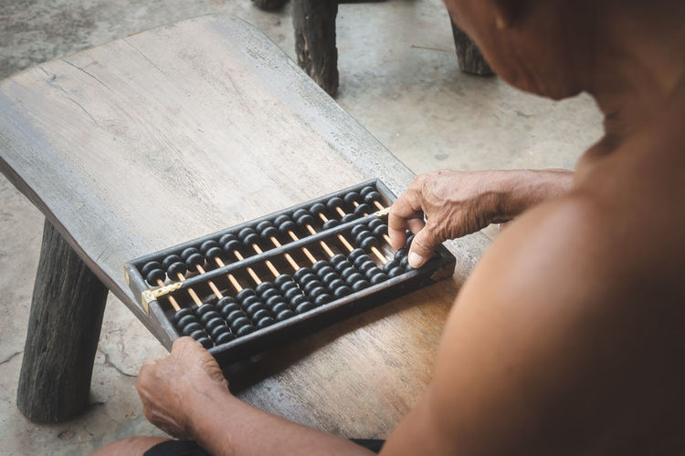 High Angle View Of Shirtless Man Counting Using Abacus