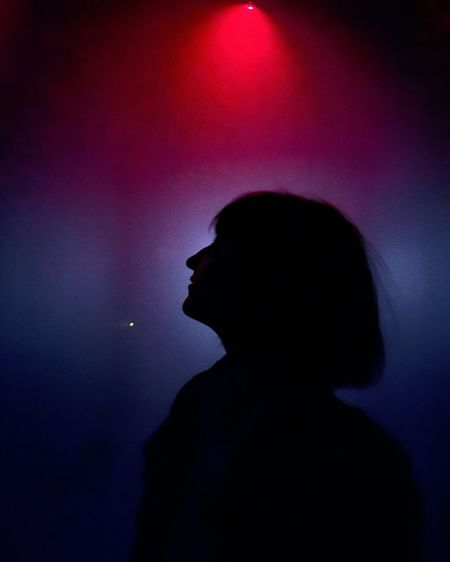 Side view portrait of silhouette man standing against illuminated light